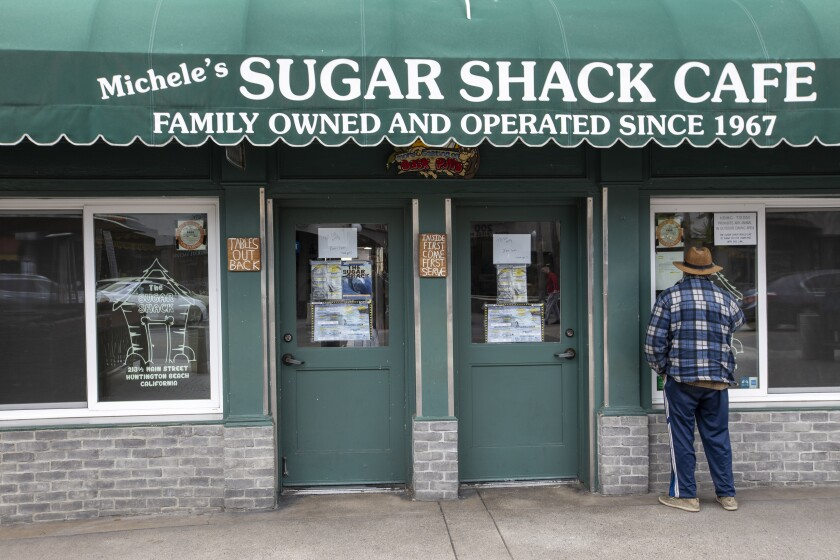 A man peers into the Sugar Shack Cafe in downtown Huntington Beach on March 18.