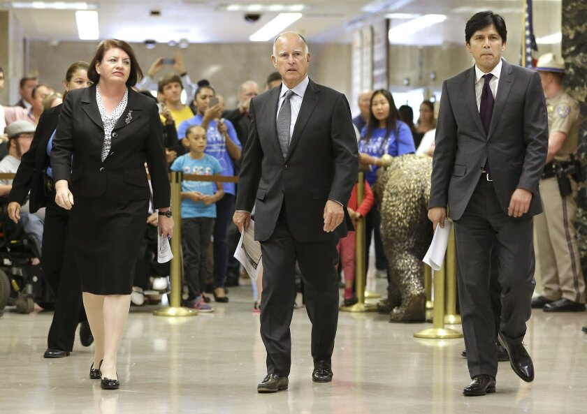 Gov. Jerry Brown, center, is flanked by Assembly Speaker Toni Atkins (D-San Diego) and Senate leader Kevin de Leon (D-Los Angeles) as they walk to a news conference last week in the Capitol to announce a budget agreement.