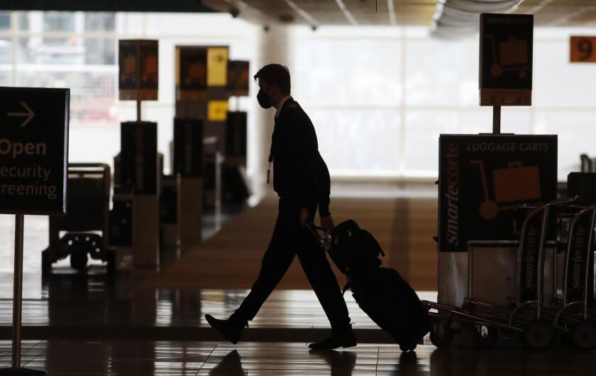 An airline crew member pulls his bags behind him as he walks through Denver International Airport.