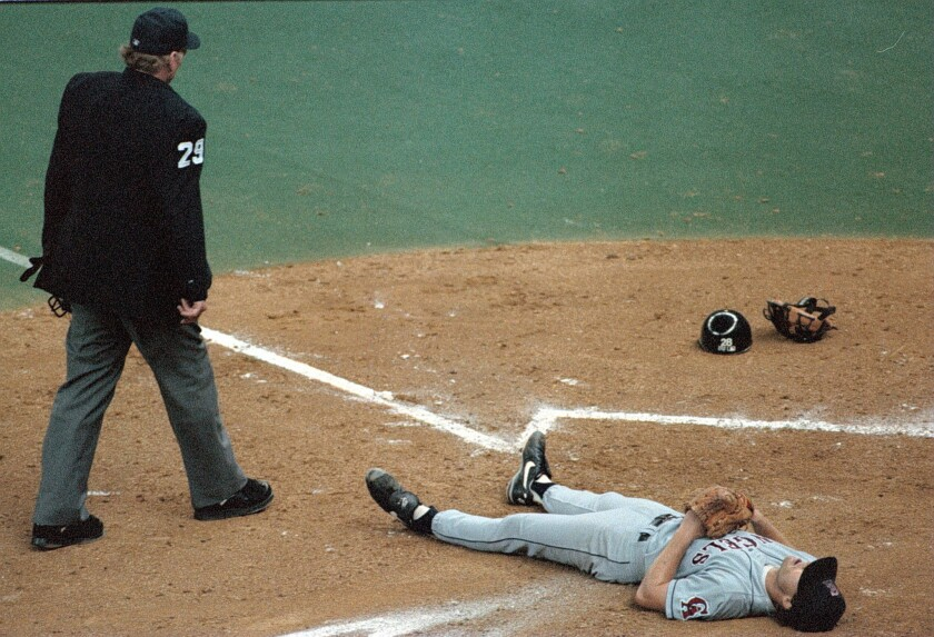 Angels pitcher Mark Langston lies dejected by the umpire at home plate after Mariners infielder Luis Sojo scored on a broken bat double with the bases loaded.