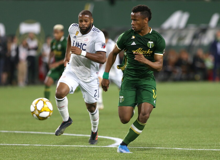 Portland Timbers' Jeremy Ebobisse is trailed by New England Revolution's Andrew Farrell (2) during an MLS soccer match Wednesday, Sept. 25, 2019, in Portland, Ore. (Sean Meagher/The Oregonian via AP)