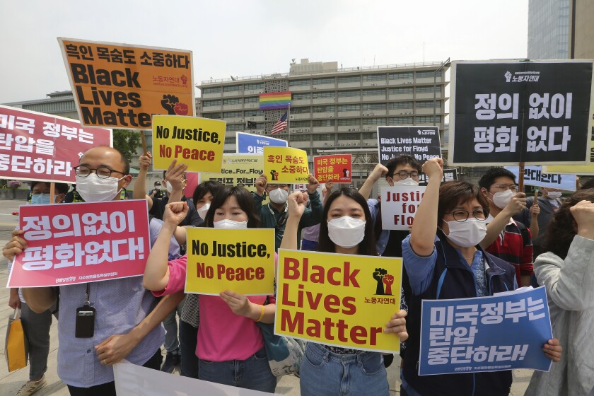 "South Korean protesters shout slogans during a protest over the death of George Floyd, a black man who died after being restrained by Minneapolis police officers on May 25, near the U.S. embassy in Seoul, South Korea, Friday, June 5, 2020. The signs read ""The U.S. government should stop oppression and there is no peace without justice."" (AP Photo/Ahn Young-joon)"