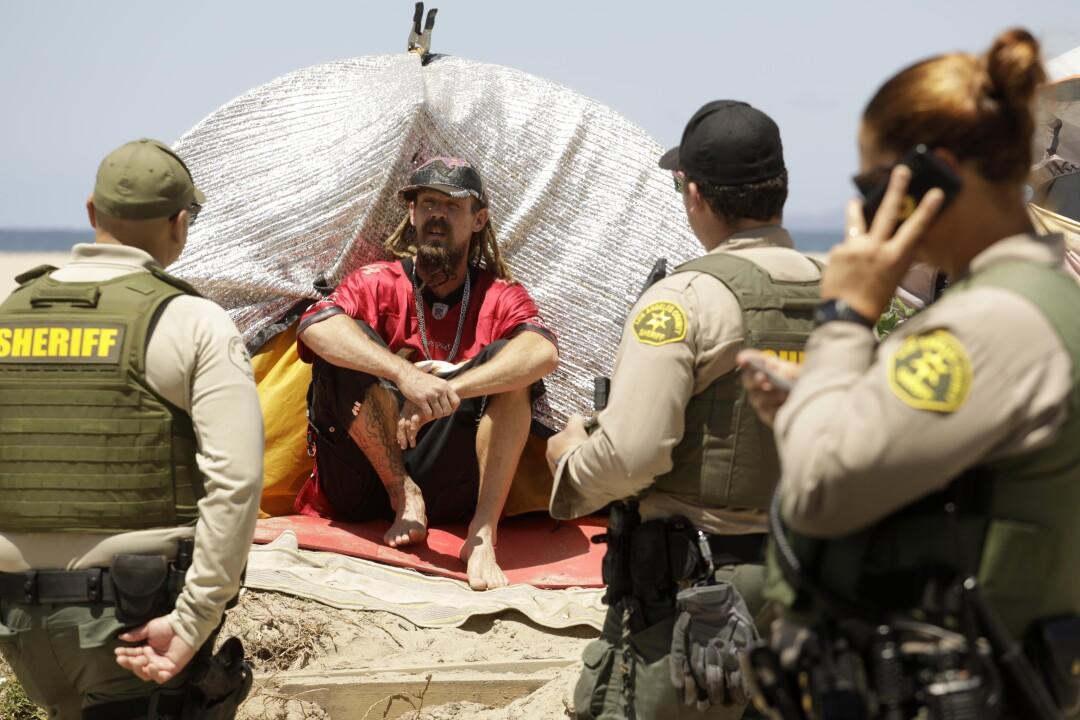 Sheriff's deputies talk to a homeless man.
