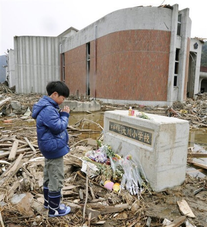 A Japanese student prays for victims at an elementary school in Ishinomaki, northeastern Japan, on Monday April 11, 2011. Exactly a month ago a massive earthquake and tsunami ravaged Japan's northeastern coastal region. (AP Photo/Kyodo News) JAPAN OUT, MANDATORY CREDIT, NO LICENSING IN CHINA, HONG KONG, JAPAN, SOUTH KOREA AND FRANCE