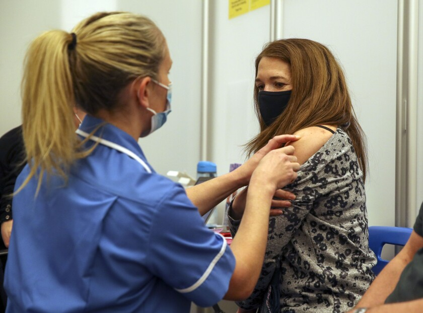 Caroline Nicolls receive an injection of the Moderna Covid-19 vaccine administered by nurse Amy Nash, at the Madejski Stadium in Reading, England, Tuesday April 13, 2021. Moderna is the third vaccine to be approved for use in the UK, and is being given to patients in England from Tuesday. (Steve Parsons/Pool via AP)