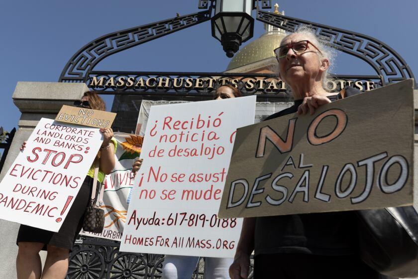 Personas de una coalición por la justicia en las viviendas llevan carteles de protesta contra los desalojos durante una conferencia de prensa junto a la legislatura de Massachusetts, en Boston, el 30 de julio del 2021. (AP Foto/Michael Dwyer)