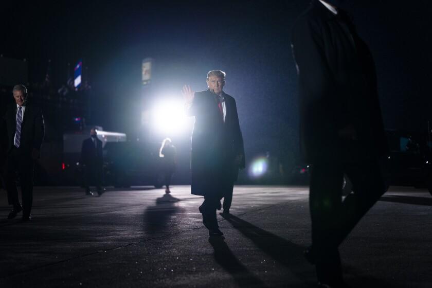 Presiden Trump melambai setelah rapat umum kampanye hari Selasa di Erie, Pa.