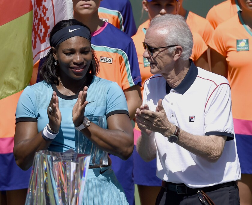 Serena Williams, left, stands with Indian Wells CEO Raymond Moore during the trophy ceremony following the final match against Belarus player Victoria Azarenka.