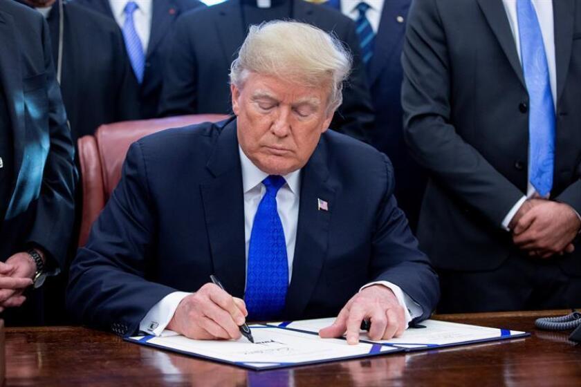 """El presidente de los Estados Unidos, Donald J. Trump, hace comentarios a los miembros de los medios de comunicación durante una ceremonia de firma del HR 390, la """"Ley de alivio y rendición de cuentas del genocidio de Irak y Siria de 2018"""", en la Oficina Oval de la Casa Blanca en Washington, DC, EE. UU. EFE/Archivo"""