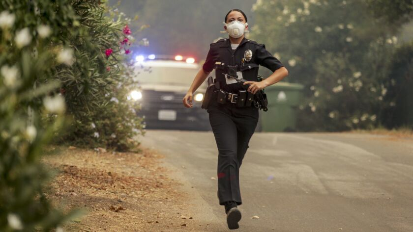 A police officer runs to evacuate residents as the La Tuna fire approaches homes in Sunland. f