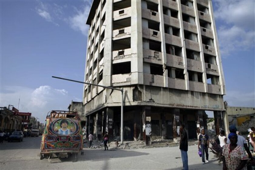 In this photo taken Aug. 25, 2010, a vehicle, with an image of Argentinean former soccer player Diego Maradona, drives past a building, damaged by the Jan. 12 earthquake, in Port-au-Prince, Haiti. By some estimates, only 2 percent of the 250 million cubic meters of debris in Port-au-Prince has been cleared, for reasons ranging from lack of equipment and money to an abysmal property records system. Meanwhile, most Haitians just live and work around the piles of debris. (AP Photo/Arnulfo Franco)