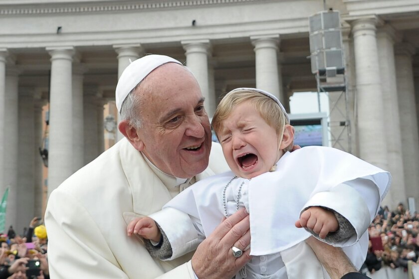 In this picture provided by the Vatican newspaper L'Osservatore Romano, 19-month-old Daniele De Sanctis, dressed up as a pope, is handed to Pope Francis as he is driven through the crowd during his weekly general audience in St. Peter's Square at the Vatican, Wednesday, Feb. 26, 2014. Francis kisse