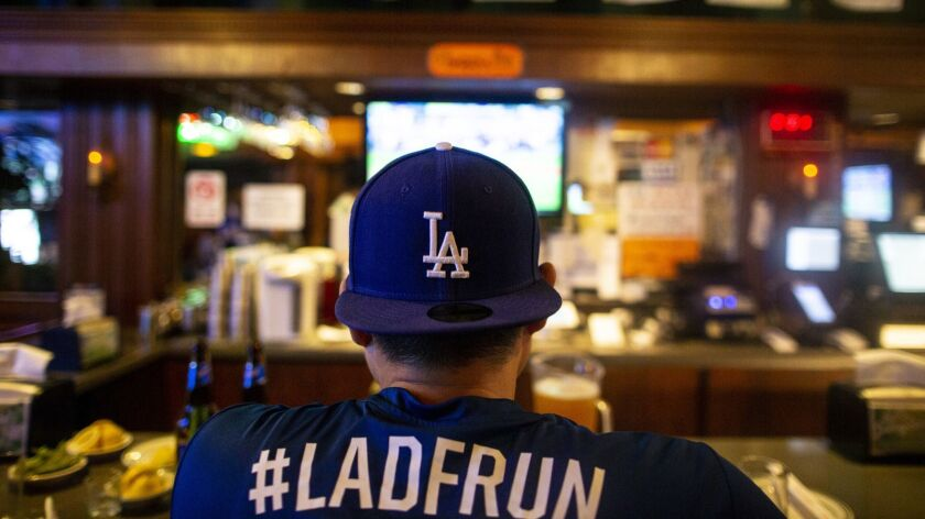 LOS ANGELES, CALIF. - OCTOBER 04: A man wearing Dodger gear sits at the bar as he and other people w