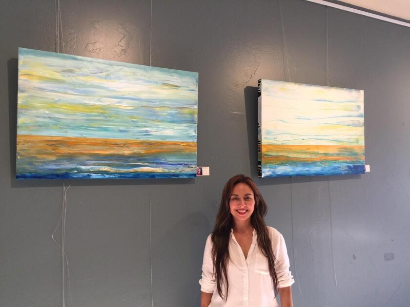 Mayra Navarro poses with her art on exhibit at Bird Rock Coffee Roasters through the month of October 2018.
