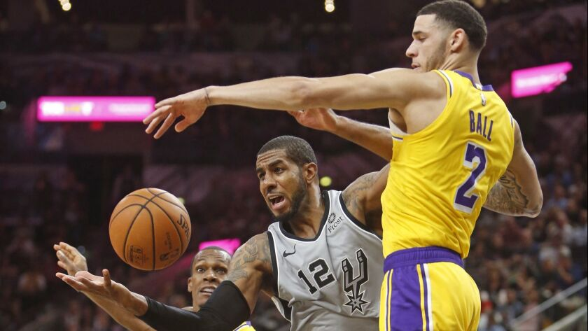San Antonio Spurs' LaMarcus Aldridge (12) battles Lakers' Lonzo Ball (2) for a rebound at AT&T Center on Saturday in San Antonio.
