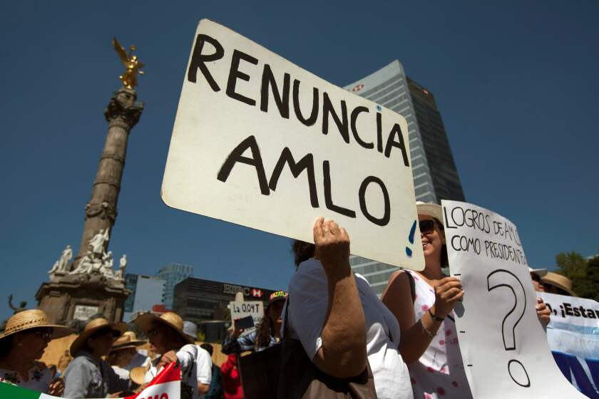 Protesters hold signs in Mexico City