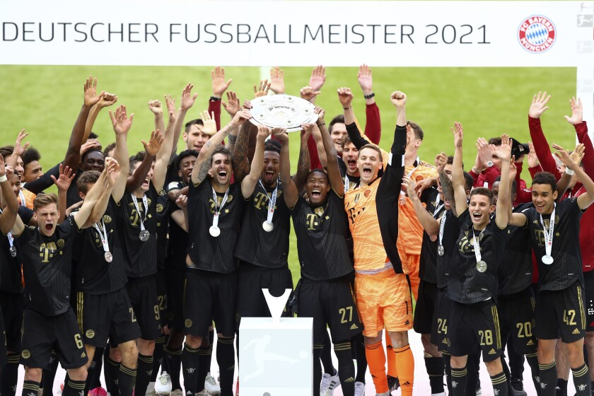 FILE - In this Saturday, May 22, 2021 file photo, Bayern's players lift the trophy after winning the Bundesliga title after the German Bundesliga soccer match between Bayern Munich and FC Augsburg at the Allianz Arena stadium in Munich, Germany. Bayern Munich will kick off the new German Bundesliga season away at Borussia Mönchengladbach after the 2021-22 fixtures were released. The game on Aug. 13 will be the first league match in charge for both teams' new coaches after Bayern hired Julian Nagelsmann from Leipzig and Gladbach brought in Adi Hütter from Eintracht Frankfurt. (AP Photo/Matthias Schrader, Pool, File)