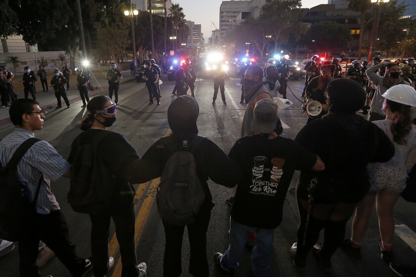 Protesters link arms and face off against the LAPD in front of L.A. City Hall Saturday.