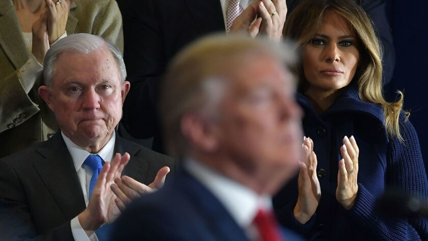 Jeff Sessions and First Lady Melania Trump listen as President Trump speaks to supporters.