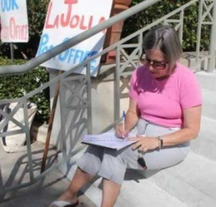 On the post office steps, Janie Emerson pens a letter to Congressman Darrell Issa.