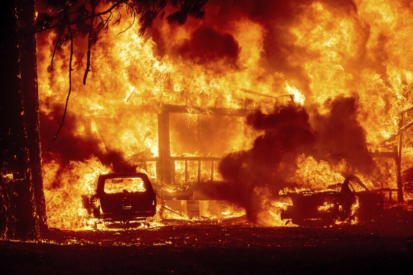 Fire envelops a house and car.