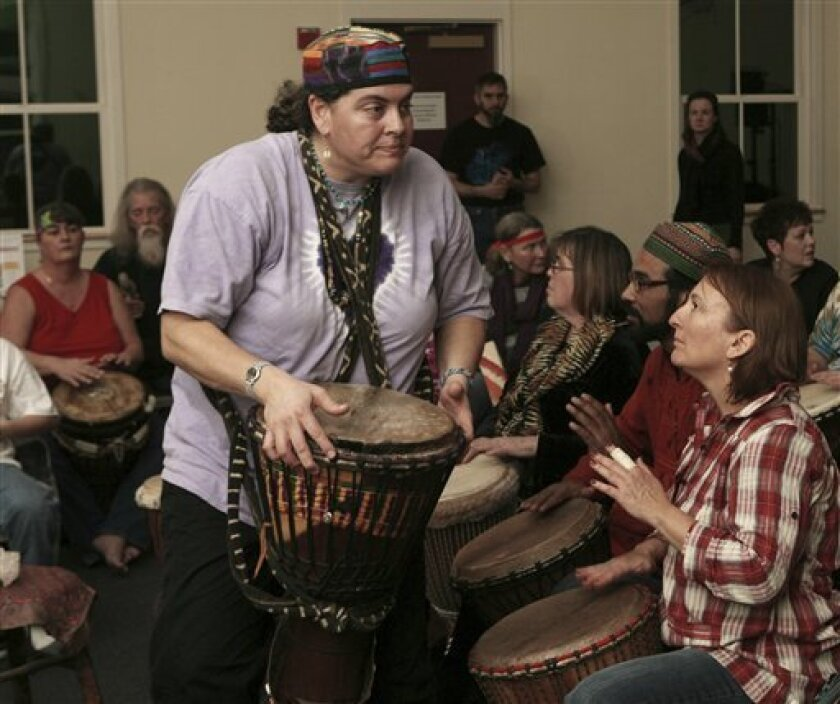 In this photo taken Saturday Jan. 23, 2010, Julie Corey leads a drum circle in Concord, N.H. (AP Photo/Jim Cole)
