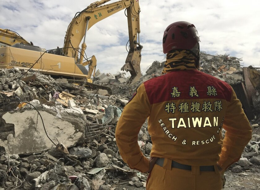 A member of rescue teams stands by as heavy excavation machinery continues to dig through the rubble of a collapsed building complex in Tainan, Taiwan, Thursday, Feb. 11, 2016. The Tainan District Prosecutors Office said in a statement Wednesday that they have approved the detention of three constr