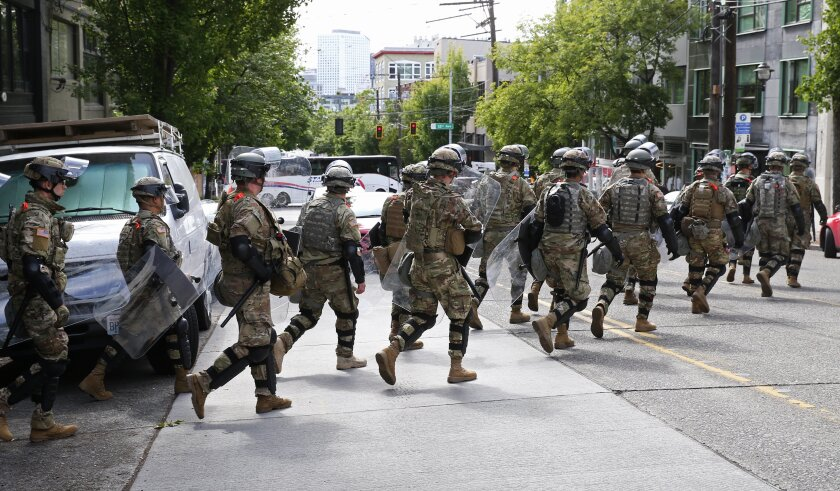 National Guard troops cross East Pike en route to the the East precinct of the Seattle Police Department, Monday, June 8, 2020, in Seattle's Capitol Hill neighborhood. Protests continued Monday across the United States over the death of George Floyd who died after being restrained by Minneapolis police officers on May 25. (Ken Lambert/The Seattle Times via AP)