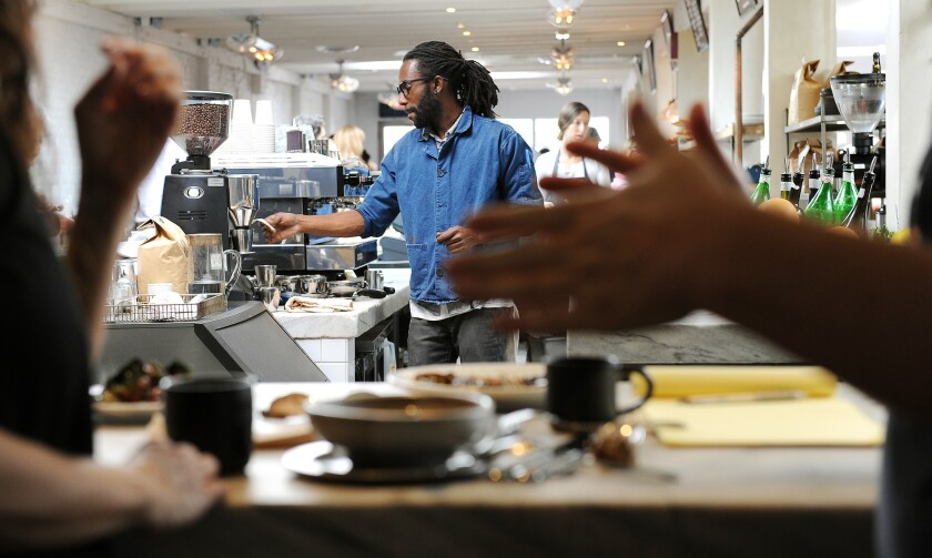 Barista Erik Rudo makes drinks as diners hang out, standing up, at Gjusta in Venice.