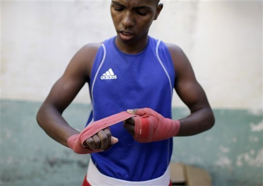 FILE - In this March 16, 2013 file photo, boxer Osain Gonzalez prepares to compete in a local boxing tournament at the Rafael Trejos boxing gym in Old Havana, Cuba. Cuba is breaking a five-decade ban on professional boxing by joining an international semi-pro league where fighters compete for sponsored teams, earn $1,000 to $3,000 a month and don't wear protective headgear, officials said Friday. Cuba will begin participating in the WSB in November. (AP Photo/Franklin Reyes, File)