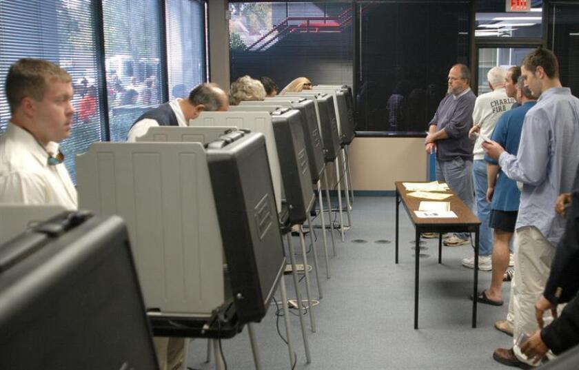 Ciudadanos estadounidenses esperan su turno para emitir su sufragio en un centro de votación de Charlotte, Carolina del Norte, el jueves 14 de octubre de 2004. EFE/Archivo