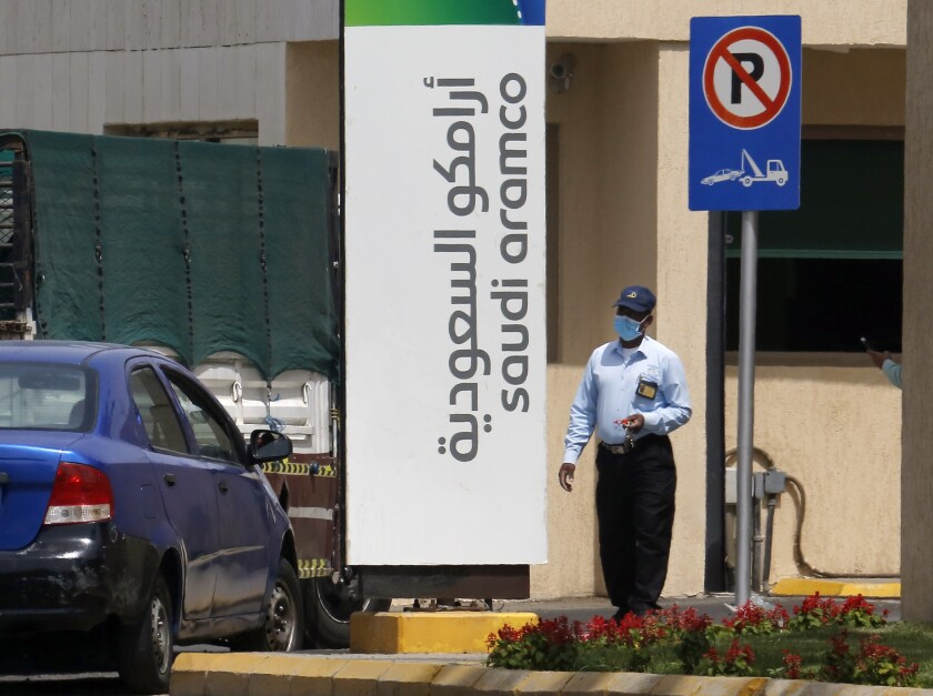 A security person wears a mask as he checks vehicles entering a compound for Saudi Aramco in Jiddah, Saudi Arabia, Monday, March 9, 2020. State oil giant Saudi Aramco sees shares drop by 10% as Riyadh stock market opens, halting trading. (AP Photo/Amr Nabil)