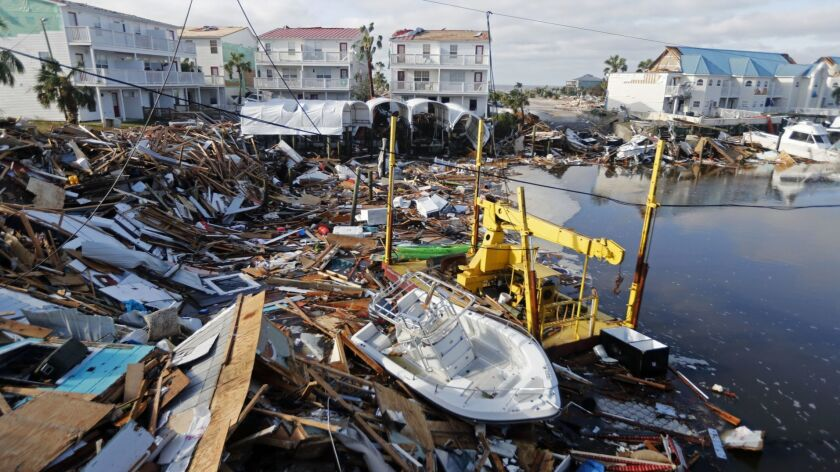 FILE - In this Oct. 11, 2018 file photo, a boat sits amidst debris in the aftermath of Hurricane Mic