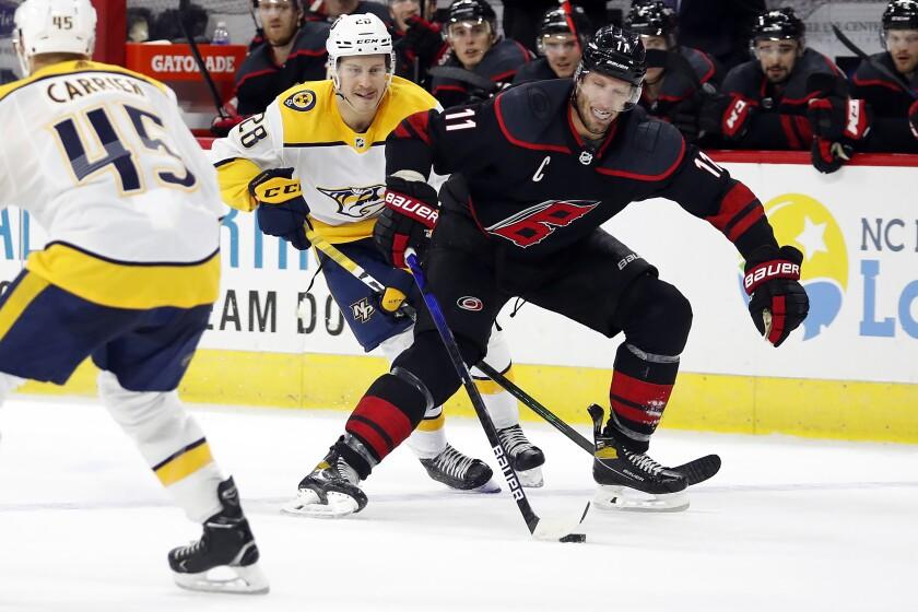 Carolina Hurricanes' Jordan Staal (11) splits the defense of Nashville Predators' Alexandre Carrier (45) and Eeli Tolvanen (28) during overtime in an NHL hockey game in Raleigh, N.C., Tuesday, March 9, 2021. (AP Photo/Karl B DeBlaker)