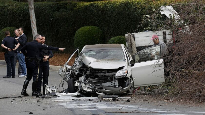 BEVERLY HILLS, CA - Jan. 15, 2016: Officers look at the damage of the Prius as the owner of the car,