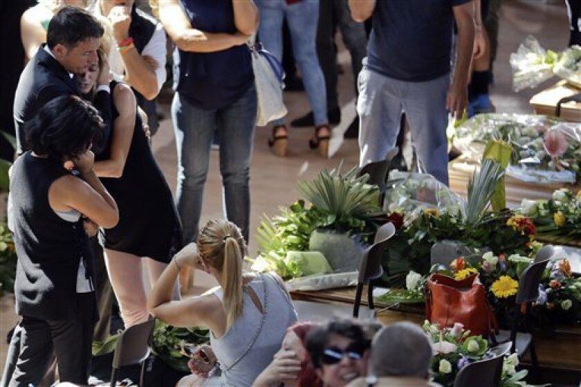 El primer ministro italiano Matteo Renzi, izquierda, conforta a una mujer al final de un funeral de estado para algunas de las víctimas del terremoto que sacudió el centro de Italia el mércoles, en Ascoli PIceno el sábado, 27 de agosto del 2016.