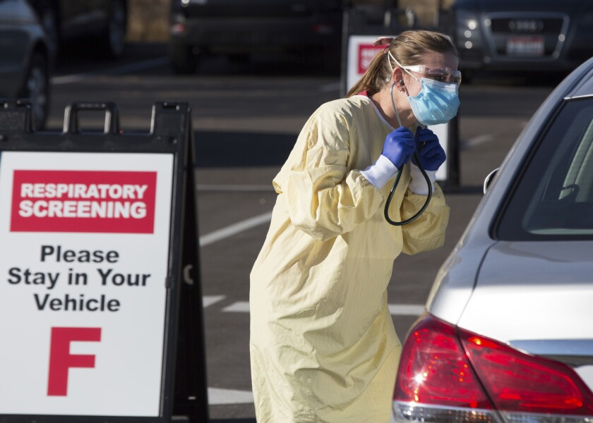 A health worker screens a motorist in the parking lot of the Primary Health Medical Group clinic in Boise, Idaho