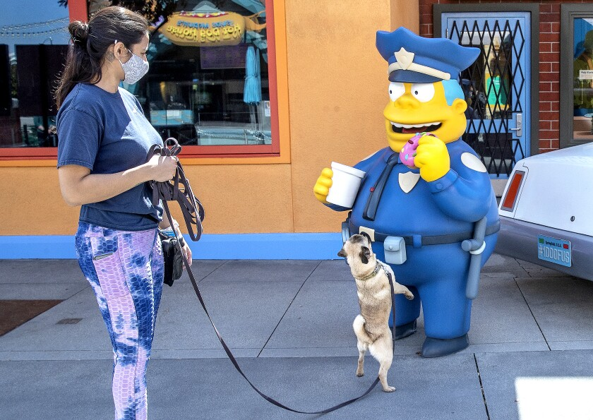 """At Universal Studios Hollywood, a woman walks a dog on a leash that's sniffing a statue of """"The Simpsons'"""" Chief Wiggum."""