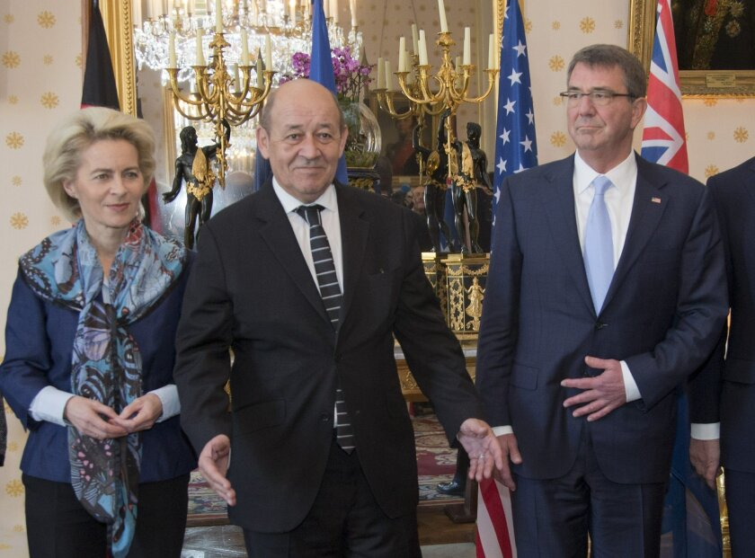 French Defense Minister Jean-Yves Le Drian, center, gestures next to German Defense Minister Ursula von der Leyen, left, and U.S. Defense Secretary Ash Carter after posing for a picture during a meeting at the Defense Ministry in Paris, Wednesday, Jan. 20, 2016. Defense chiefs from seven countries meet in Paris to plan to intensify the fight against Islamic State group extremists. (AP Photo/Jacques Brinon)