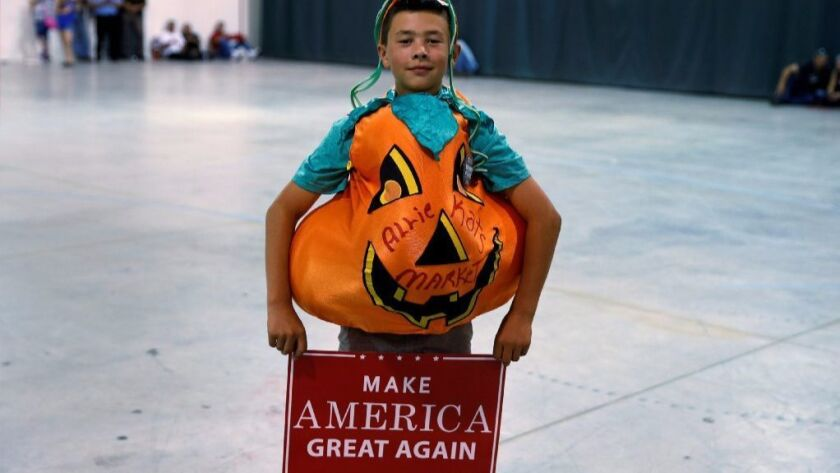 A youth in a pumpkin outfit poses for a photo as he waits for Republican presidential nominee Donald Trump before a campaign event in Dimondale, Michigan, U.S., August 19, 2016.