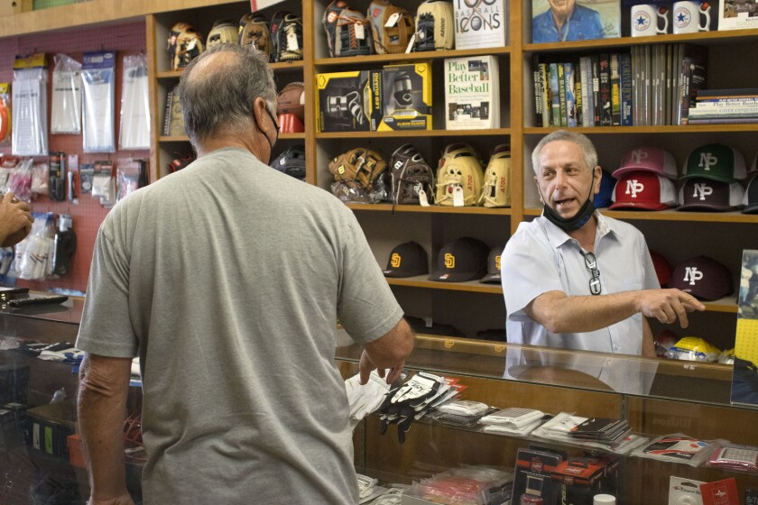 Gregg Schloss, right, chats with friend and customer Jimmy Morstad on Tuesday at A&B Sporting Goods in North Park.