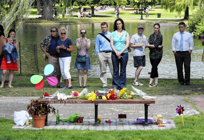 """People pause at a memorial to Robin Williams in Boston's Public Garden, where a scene of his movie """"Good Will Hunting"""" was filmed."""