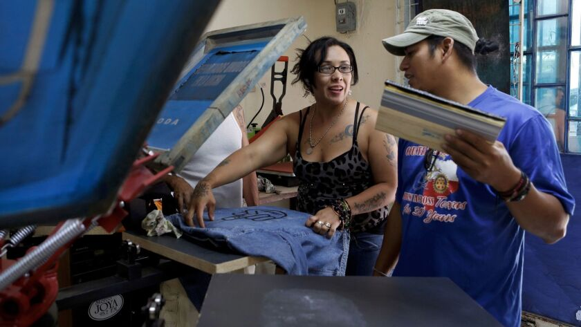 Diego Maria, right, talks with Ana Laura Lopez as she screen-prints T-shirts at a shop Maria opened