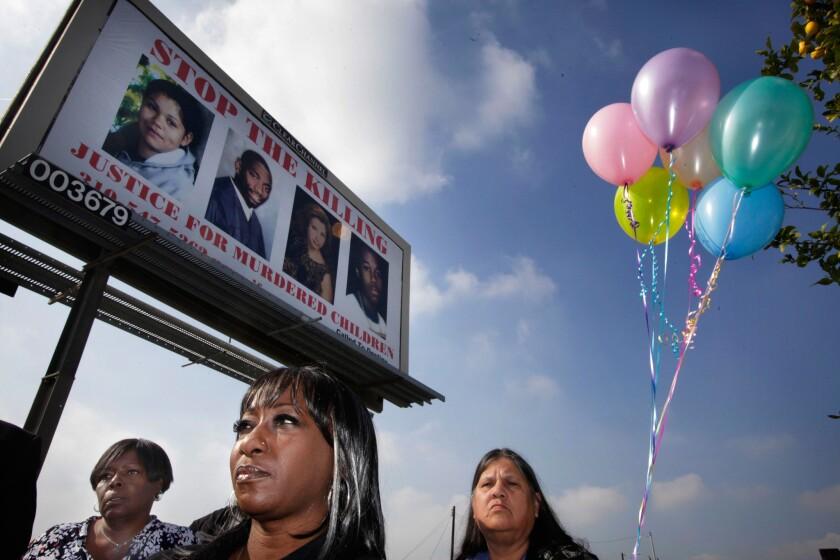 Activists Vicky Lindsey, center, with Pamela Carolina, left, and Teresa Haro under a billboard showing homicide victims.