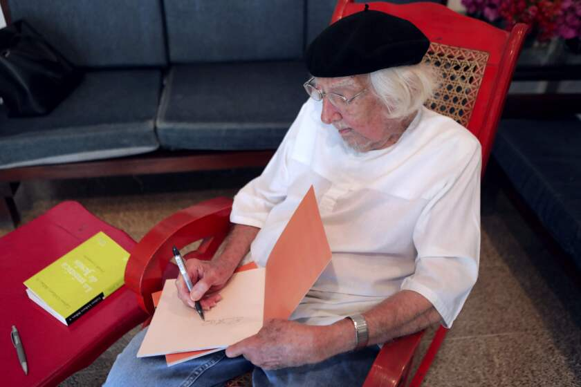 Nicaraguan poet and priest Ernesto Cardenal signs books in his home in Managua in 2018.