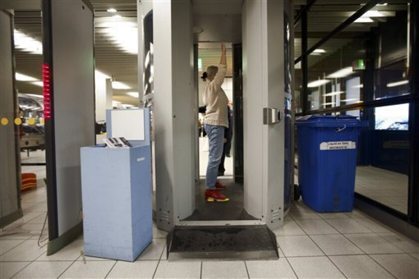 A passenger is checked inside a body scanner at Schiphol airport, Netherlands, Monday, Dec. 28, 2009. The scanners, like small walk-in closets, reveal the outline of a passenger's body to detect any concealed objects under the clothing. Body scanners that peer under a passenger's clothing might hav