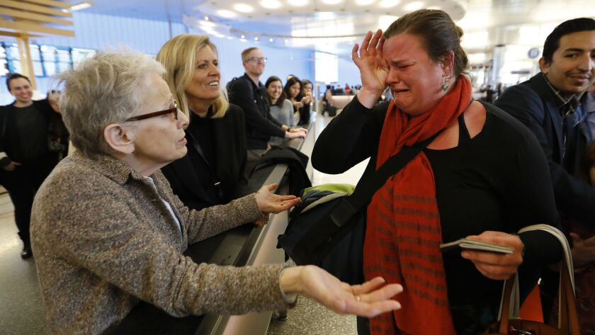 Nora Phillips, right, is in tears as she is greeted by fellow immigration attorney Helen Sklar, left, as Phillips arrived at Los Angeles International Airport. Phillips was sent home when her U.S. passport was flagged while she tried traveling to Mexico.