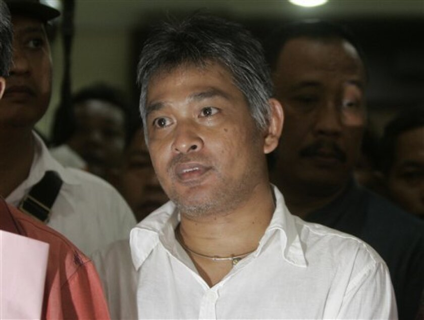 Former editor-in-chief of Playboy Indonesia magazine Erwin Arnada is escorted by police officers to a detention car that will take him to a prison at a prosecutor's office in Jakarta, Indonesia, Saturday, Oct. 9, 2010. Arnada starts his two-year jail sentence Saturday for publishing pictures of scantily clothed women. (AP Photo/Irwin Fedriansyah)