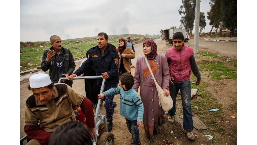 Under the threat of a sniper down the road behind them, residents flee the conflict on foot in West Mosul, in Nineveh Province, on March 15, 2017.