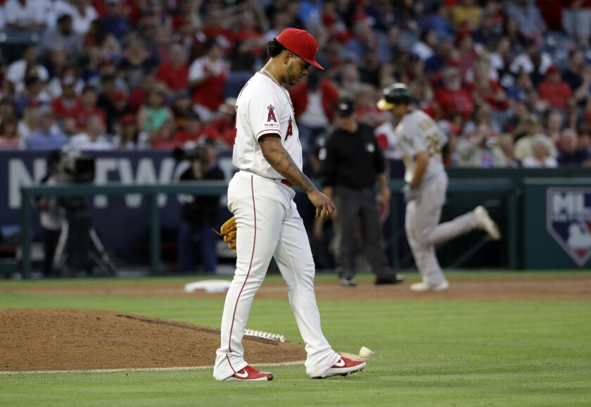 Angels pitcher Felix Pena walks off the mound after giving up a three-run home run to the Athletics' Matt Olson, background right, during the third inning Friday at Angel Stadium.